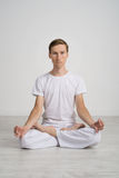 Young man meditating in Lotus position on the floor Stock Photo