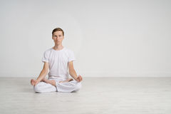 Young man meditating in Lotus position on the floor Royalty Free Stock Photography
