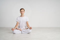 Young man meditating in Lotus position on the floor Stock Photos