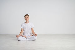 Young man meditating in Lotus position on the floor Stock Photography