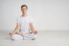 Young man meditating in Lotus position on the floor Royalty Free Stock Images