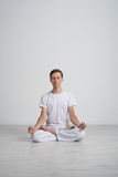 Young man meditating in Lotus position on the floor Stock Images