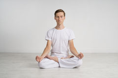 Young man meditating in Lotus position on the floor Royalty Free Stock Photo
