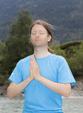 Young man meditating in Namaste Pose outdoors in nature Royalty Free Stock Photos