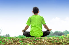 Young man meditating outdoors Stock Images