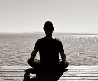 Young man meditating outdoors seen from behind Stock Photos