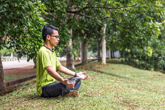 Young man meditating outdoors Royalty Free Stock Image