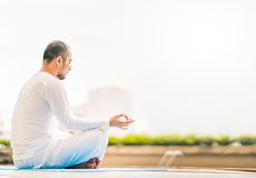 Young man meditating by swimming pool, yoga or relax concept, city view background with copy space Stock Images