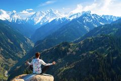 Young man meditating on top of the mountain. The image, in which a young man meditating on a mountain on the background of a very beautiful valley royalty free stock image