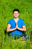 Young man meditation on green grass Royalty Free Stock Image