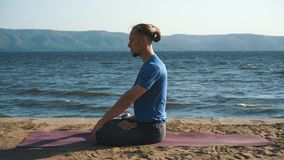Young man in meditation near the ocean, mountains on background stock video