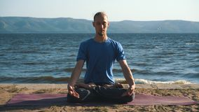 Young man in meditation near the ocean, mountains on background stock video footage