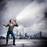 Young man with megaphone. Portrait of young man shouting loudly using megaphone Stock Photo