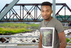 Young man on metal bridge structure, river and railway beams Royalty Free Stock Images