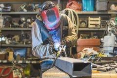 Metal shop welding in progress young worker welding metal rods royalty free stock image