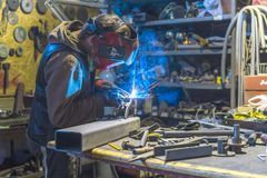 Metal shop welding in progress sparks fly while young man`s work stock photography