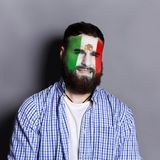 Young man with Mexica flag painted on his face. Face of young bearded man painted with flag of Mexica. Football or soccer team fan, sport event, faceart and Royalty Free Stock Photo
