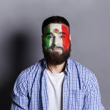 Young man with Mexica flag painted on his face. Face of young bearded man painted with flag of Mexica. Football or soccer team fan, sport event, faceart and Royalty Free Stock Photos