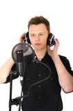 Young man with microphone on white background. Young man with headphones and studio mic on white background stock images