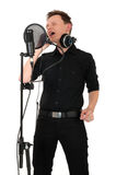 Young man with microphone on white background. Young man singing in studio on white background royalty free stock photography
