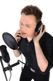 Young man with microphone on white background. Young man with headphones and studio mic singing on white background royalty free stock photos