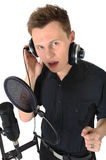 Young man with microphone on white background. Young man with headphones and studio microphone on white background stock images