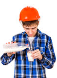 Young Man with a Milk. Young Man in Hard Hat pour the Milk in a Glass Isolated on the White Background Royalty Free Stock Photo