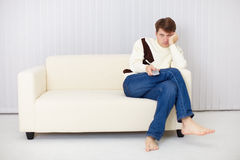 Young man misses sitting on sofa at the TV Royalty Free Stock Photo