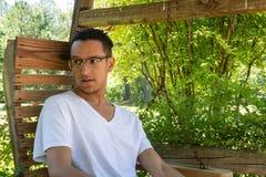 Young man mixed race looking away, backyard swing with greenery