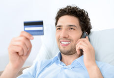 Young man on mobile with credit card Royalty Free Stock Photos