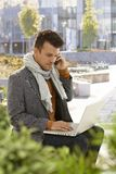 Young man with mobile and laptop outdoors Stock Photo