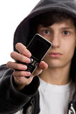 Young man with mobile phone. Close-up portrait of young man wearing hooded sweatshirt showing mobile phone. Focus on phone Stock Photography