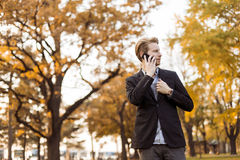 Young man with mobile phone in the autumn park Royalty Free Stock Photography