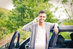 Man with mobile phone in the car. Young man with mobile phone in the car Royalty Free Stock Photography
