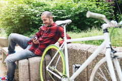 Young man with mobile phone and fixed gear bicycle. Portrait of handsome young man with mobile phone and fixed gear bicycle in the city Royalty Free Stock Images