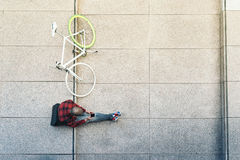 Young man with mobile phone and fixed gear bicycle. Portrait of handsome young man with mobile phone and fixed gear bicycle in the city Royalty Free Stock Image