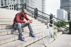 Young man with mobile phone and fixed gear bicycle. Portrait of handsome young man with mobile phone and fixed gear bicycle in the city Royalty Free Stock Photos