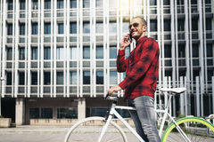 Young man with mobile phone and fixed gear bicycle. Portrait of handsome young man with mobile phone and fixed gear bicycle in the city Stock Photos
