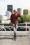 Young man with mobile phone and fixed gear bicycle. Portrait of handsome young man with mobile phone and fixed gear bicycle in the city Stock Image