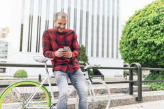 Young man with mobile phone and fixed gear bicycle. Royalty Free Stock Images