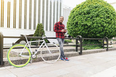 Young man with mobile phone and fixed gear bicycle. Portrait of handsome young man with mobile phone and fixed gear bicycle in the city Stock Photography