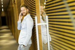 Young man with mobile phone in office Royalty Free Stock Photography