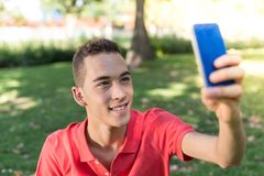 Young man with mobile phone. In the park Royalty Free Stock Images