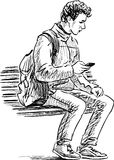 Young man with a mobile phone sits on a park bench Royalty Free Stock Photo