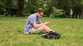 Young man with mobile phone sitting on a grass. Young man with mobile phone sitting on a grass Royalty Free Stock Images