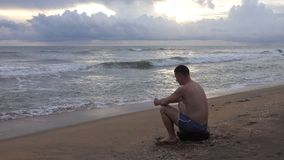 Young man with mobile phone on the tropical ocean beach at sunset. The coast of Sri Lanka stock video