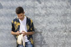 Young man with mobile phone on the wall. With space for ads or text royalty free stock photo