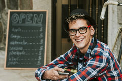 Young man with mobile in store front. Enterprising young man with mobile phone in your small business Royalty Free Stock Photography