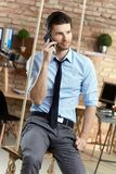 Young man on mobilephone. Young businessman sitting on swing in office, talking on mobilephone Royalty Free Stock Photography
