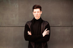 The young man model in a black jacket poses at a wall. image toned Stock Images